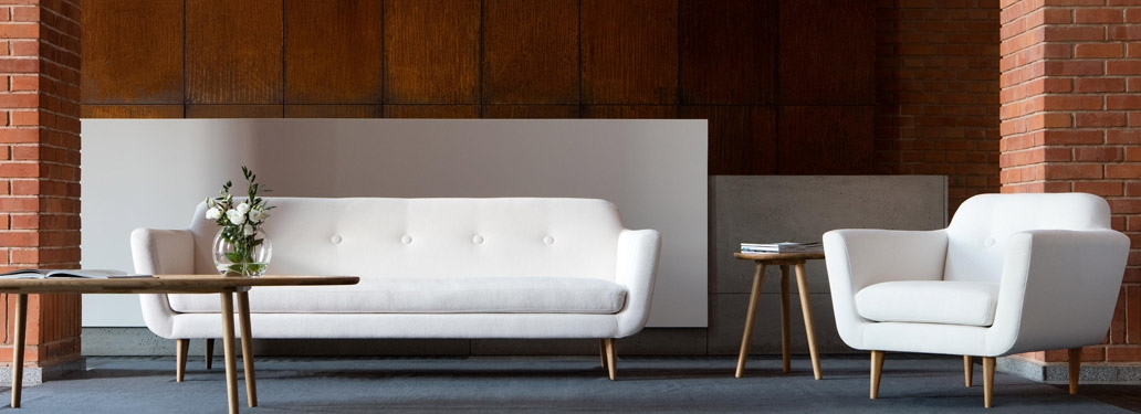 White 2 Seater Corner Sofa Designed By Adventures In Furniture. These Handmade Sofas Have Endless Fabric Choices To Fit Every Space In Your Home. This Sofa On Show Has Wooden Legs With A Matching Coffee Table