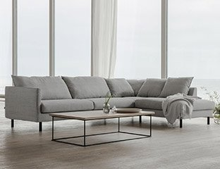 White 3 Seater Corner Sofa Designed By Adventures In Furniture. These Handmade Sofas Have Endless Fabric Choices To Fit Every Space In Your Home. This Sofa On Show Has Wooden Legs With A Matching Coffee Table