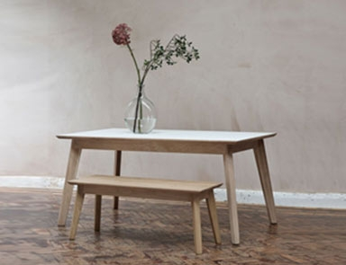 White Fenix dining table with matching bench By Adventures In Furniture.